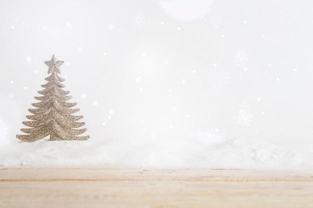 Houten raad dichtbij stuk speelgoed kerstboom op hoop van sneeuw Gratis Foto