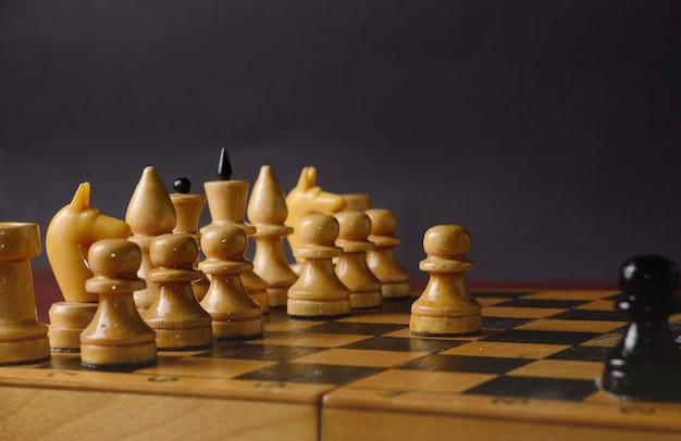 Houten schaken. witte pion tegen de rest van de figuren op het bord Premium Foto