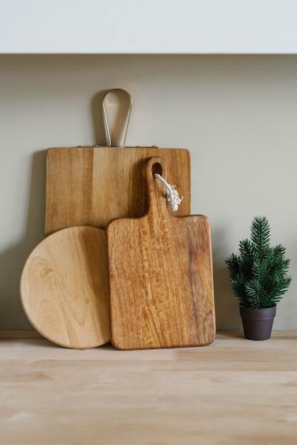 Houten snijplanken in verschillende vormen en een kleine kerstboom in een pot Premium Foto