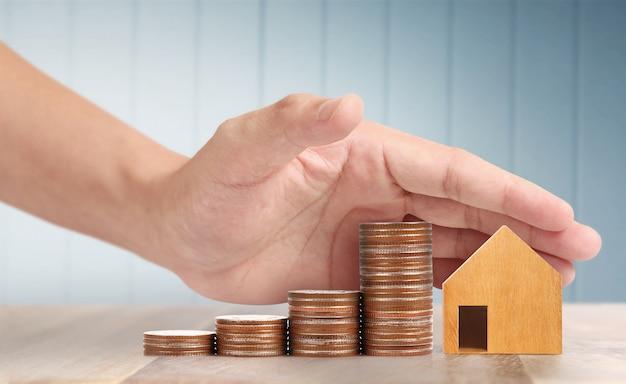 Houten speelgoed huis hypotheek eigendom thuis concept kopen voor familie, munten in de hand Premium Foto