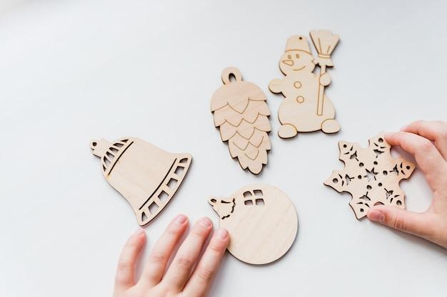 Houten speelgoed in handen van kinderen, klaar om kerstversiering te maken. houten kerstboomversieringen op witte achtergrond. hobby, diy, kids vakantie ambachten. kopieer ruimte Premium Foto