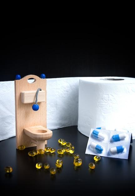Houten speelgoed toilet, capsules en papier op zwarte achtergrond Premium Foto