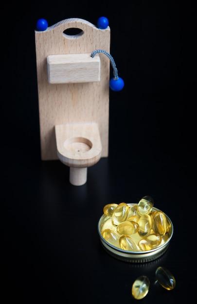 Houten speelgoedtoilet en gele capsules Premium Foto