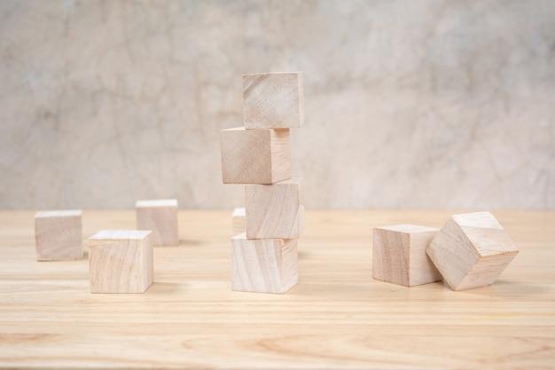 Houten stuk speelgoed kubussen op houten lijstang grijze achtergrond Premium Foto