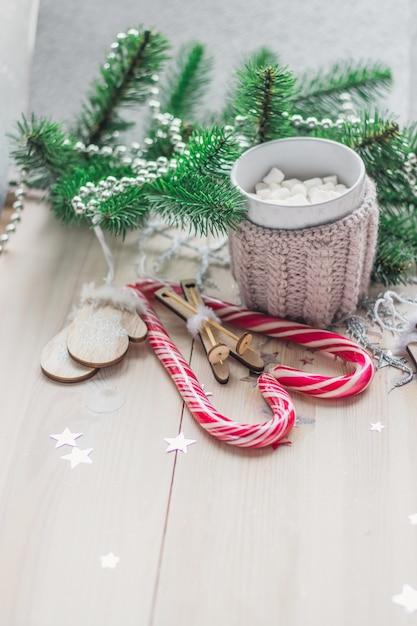 Houten tafel bedekt met snoepgoed, marshmallows en kerstversieringen onder de lichten Gratis Foto