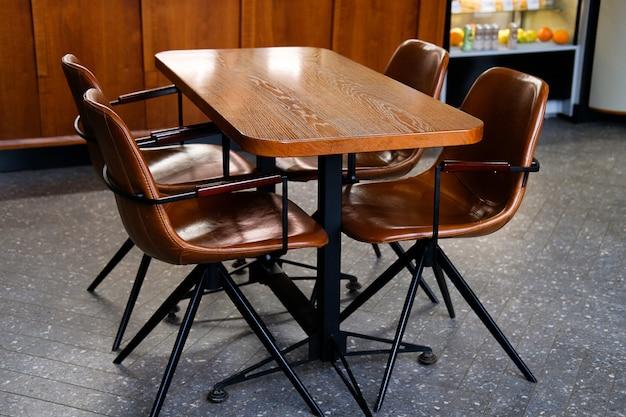 Houten tafel en lederen stoelen of stoelen, in een café, kantoor of kamer. Premium Foto