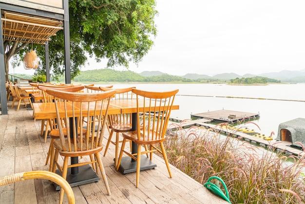Houten tafel en stoel in café-restaurant aan een meer Premium Foto
