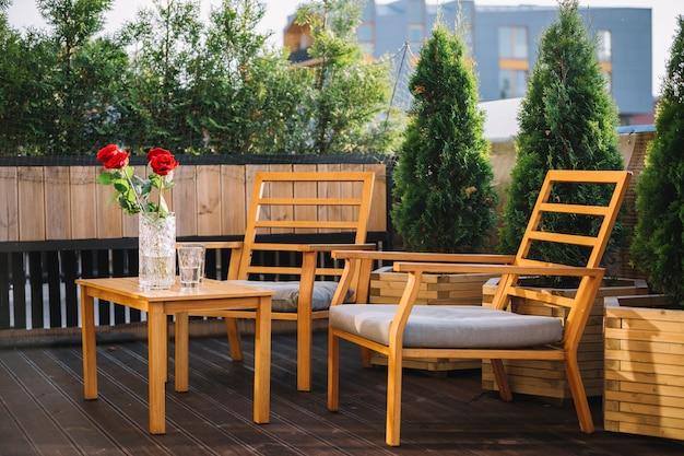 Houten tafel en stoelen op een terras op een dak foto gratis
