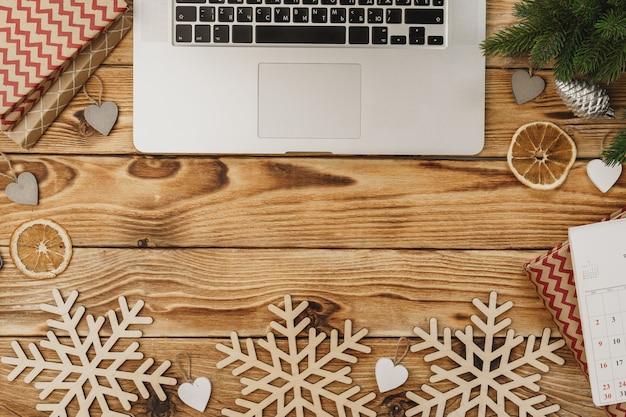 Houten tafel met kantoorapparatuur en kantoorbehoeften omringd met nieuw jaar feestelijk decor, mening van hierboven Premium Foto