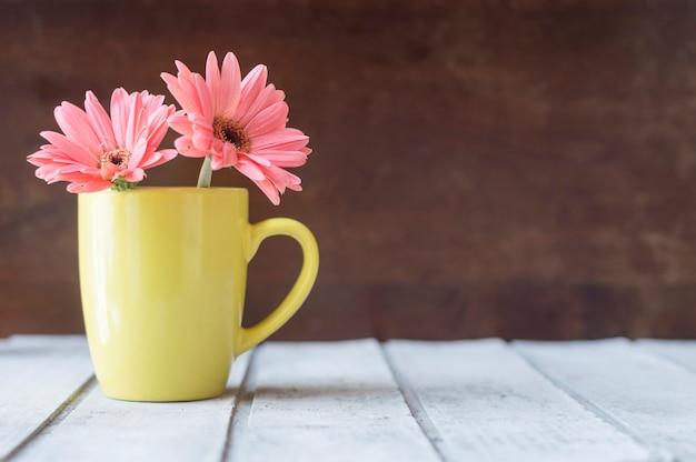 Houten tafel met mooie bloemen op gele mok Gratis Foto