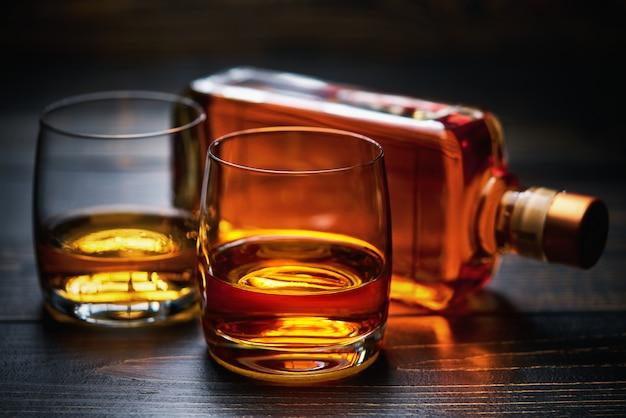Houten tafel met twee shots whisky en volle fles Premium Foto
