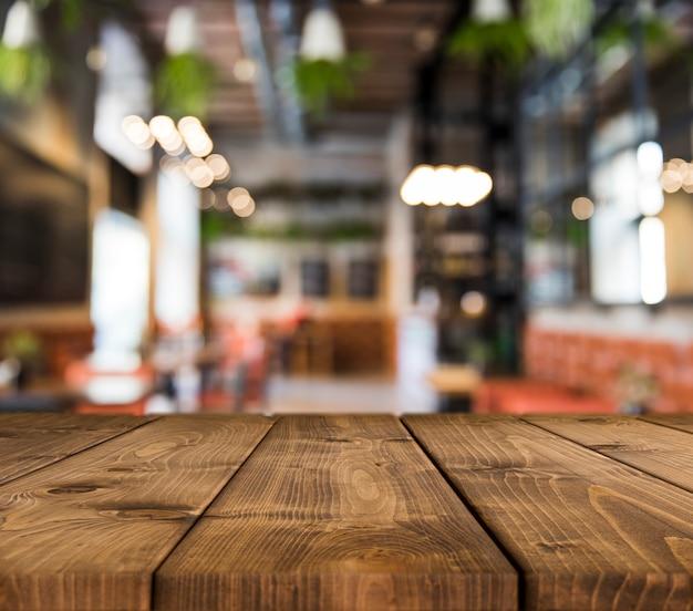 Houten tafel met wazig restaurant scène Gratis Foto