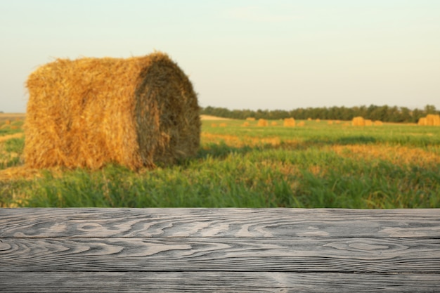 Houten tafel tegen veld met stro broodjes. landbouw concept. mockup Premium Foto