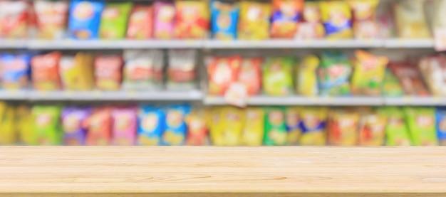 Houten tafelblad met supermarkt supermarkt schappen met chips snack abstracte achtergrond wazig Premium Foto
