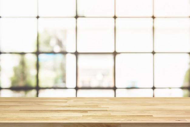 Houten tafelblad met vervagen helder vierkant transparant venster van café op de achtergrond Premium Foto