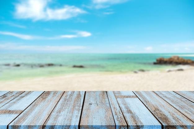 Houten tafelblad met wazig natuurlijke zee van tropisch strand en blauwe hemel, zomer vakantie achtergrond Premium Foto