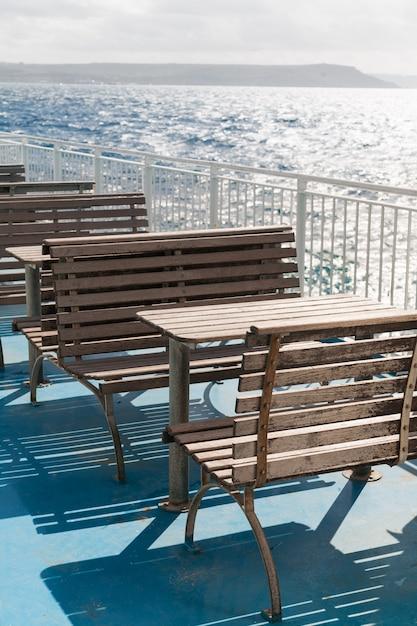 Houten tafels en banken op het bovendek van de veerboot. Premium Foto
