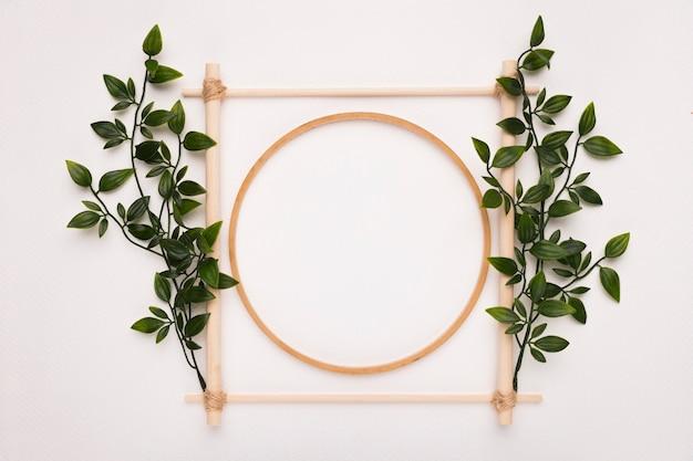 Houten vierkant en cirkelkader dat met groene bladeren op witte achtergrond wordt verfraaid Gratis Foto