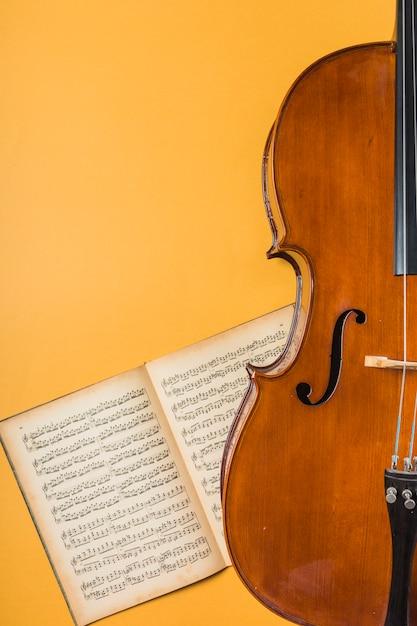 Houten viool met koord en muzikaal notitieboekje op gele achtergrond Gratis Foto