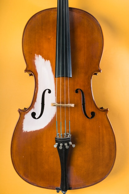 Houten viool met koord op gele achtergrond Gratis Foto