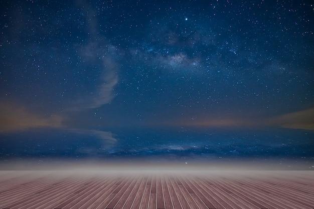 Houten vloer en achtergrond van de melkweghemel 's nachts Premium Foto