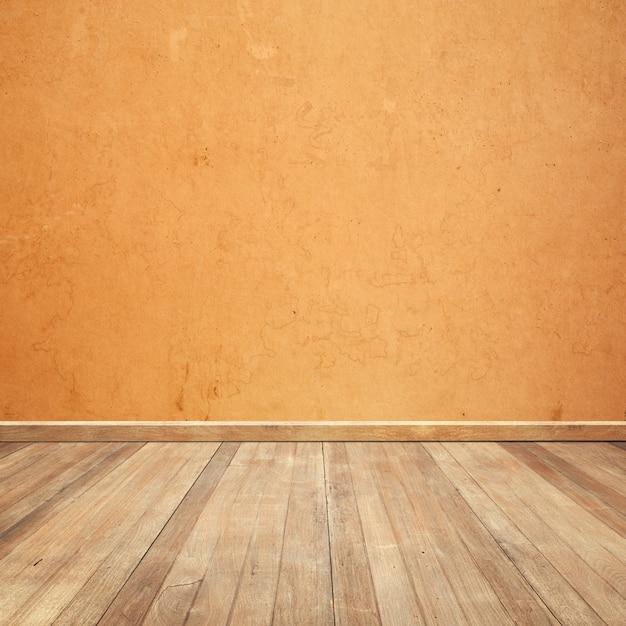 Houten vloer met een oranje muur achtergrond Gratis Foto