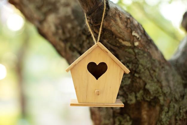 Houten vogelhuisje opknoping van boom in herfst tuin. concept voor nieuw  huis. vogelhuisje of vogelhuisje in de zomerzon met natuurlijke groene  bladerenachtergrond. | Premium Foto