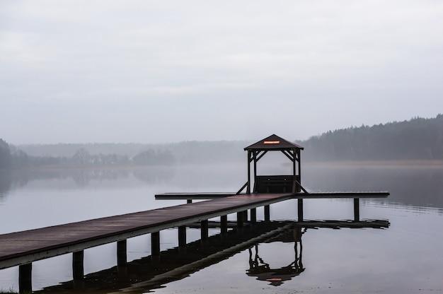 Houten weg boven het water dat door bomen met een mistige achtergrond wordt omringd Gratis Foto