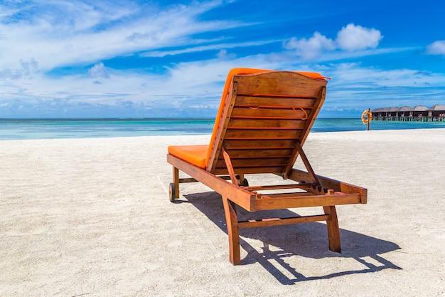 Houten zonnebank op tropisch strand in de malediven Premium Foto