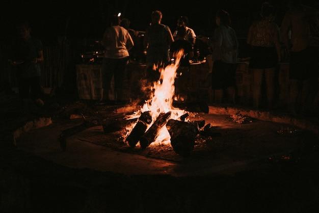 Houtgestookte mensen in een kampvuuravond Gratis Foto
