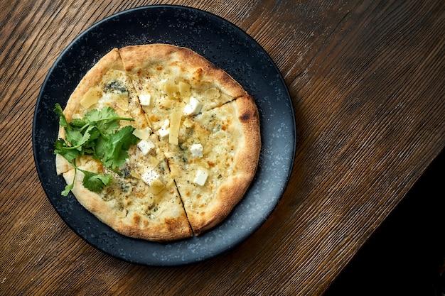 Houtgestookte pizza met 4 soorten kaas en witte saus op een houten achtergrond. pizzette een soort italiaanse pizza Premium Foto
