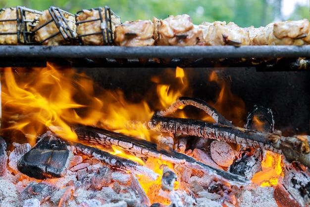 Houtskool barbecue grill met vlam en koken van vlees in zachte focus. Premium Foto