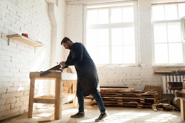 Houtwerk en constructie. timmerman met handzaag voor het hakken van houten plank Gratis Foto