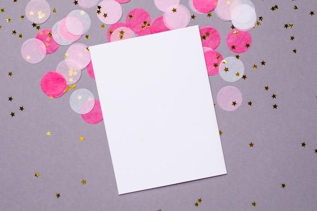 Huidige kaart en roze confetti met gouden sterren op grijs Premium Foto