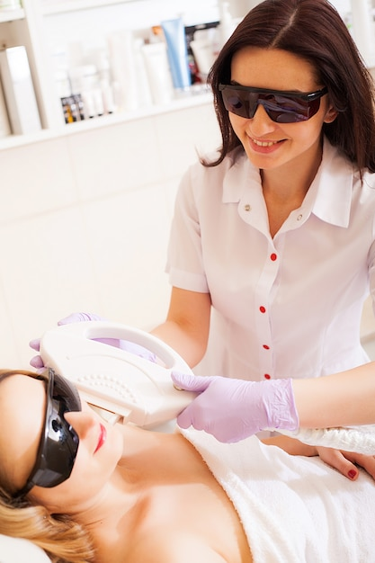 Huidsverzorging. volwassen vrouw die de verwijdering van het laserhaar in professionele schoonheidssalon hebben Premium Foto