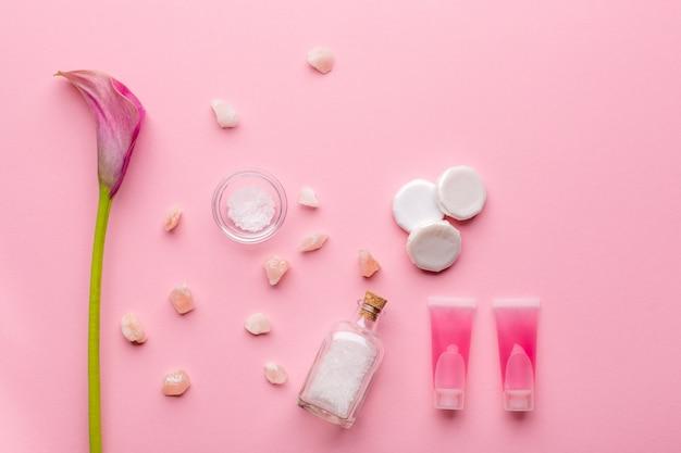 Huidverzorging concept. zeezout, zeep, micellair water en calla leliebloem op een roze pastelkleurachtergrond Premium Foto