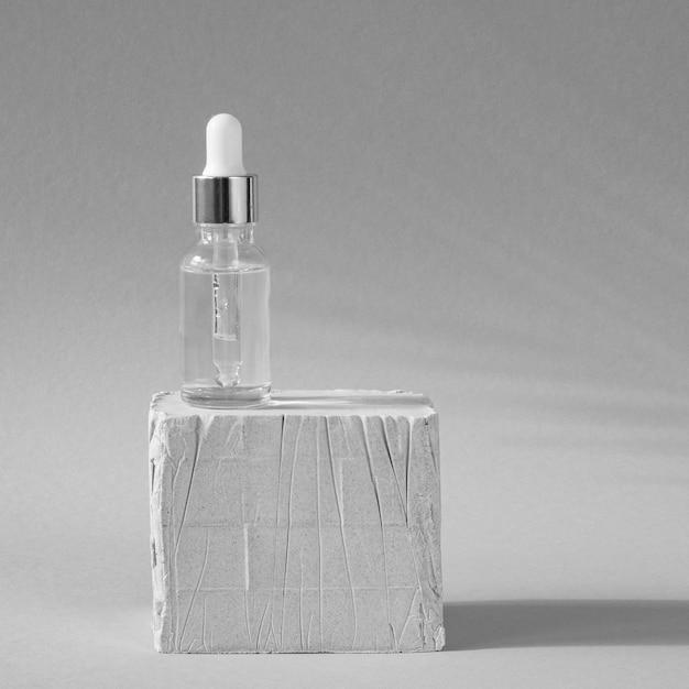 Huidverzorging druppelaar op witte steen Gratis Foto