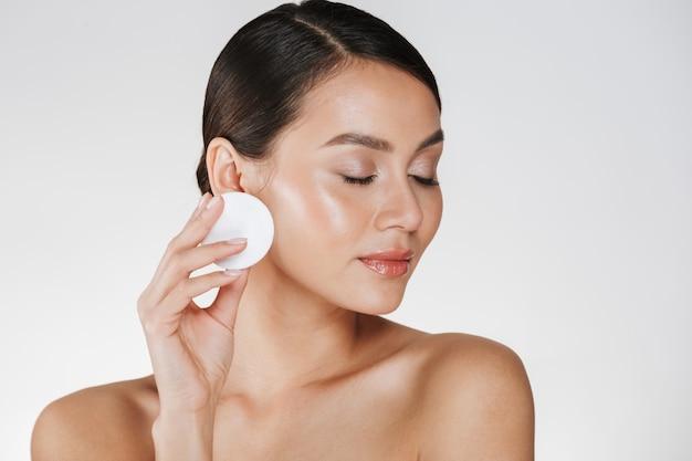 Huidverzorging en gezonde behandeling van vrouw make-up verwijderen uit gezicht met wattenschijfje, geïsoleerd op wit Gratis Foto