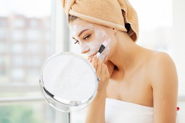 Huidverzorging, jonge vrouw met mooie gezichtshuid die masker op gezicht toepast Premium Foto