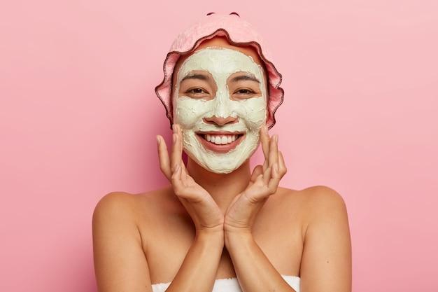Huidverzorging voor alle leeftijden. gelukkige aziatische dame met afbladderend kleimasker op gezicht, heeft schoonheidsbehandelingen, ziet er aangenaam uit, raakt wangen aan, draagt een douchemuts Gratis Foto
