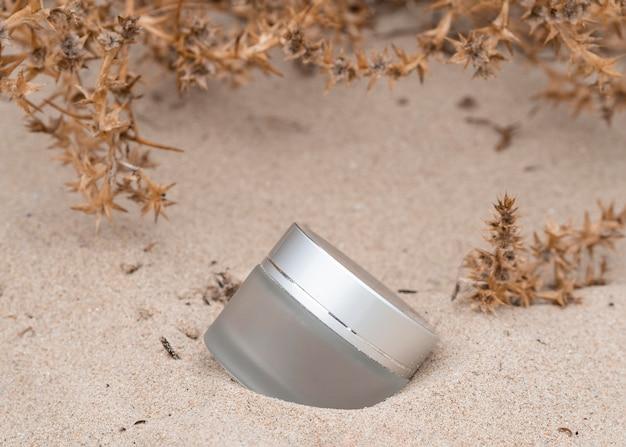 Huidverzorgingsproduct arrangement in zand Gratis Foto
