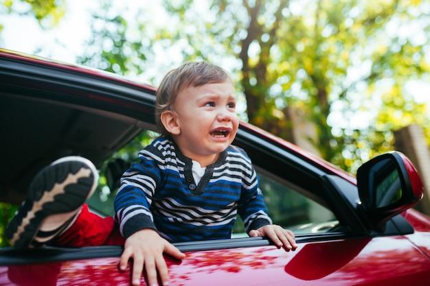 Huilende babyjongen in auto. Premium Foto