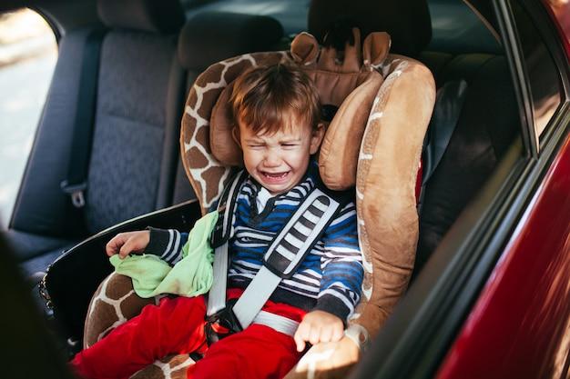 Huilende babyjongen in een veiligheidsautozetel Premium Foto