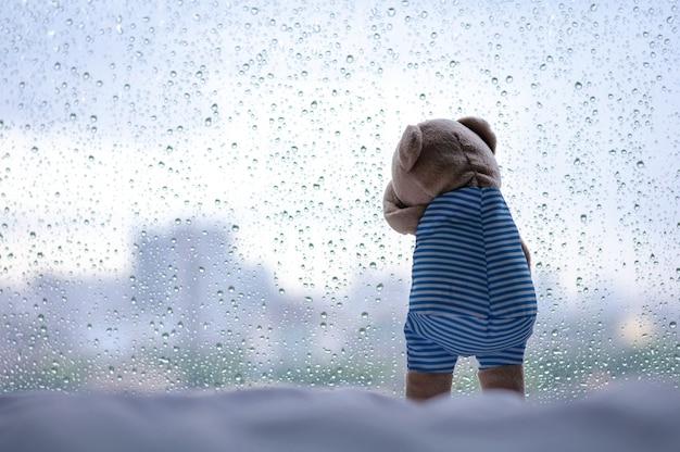 Huilende teddybeer bij het raam in regenachtige dag. Premium Foto