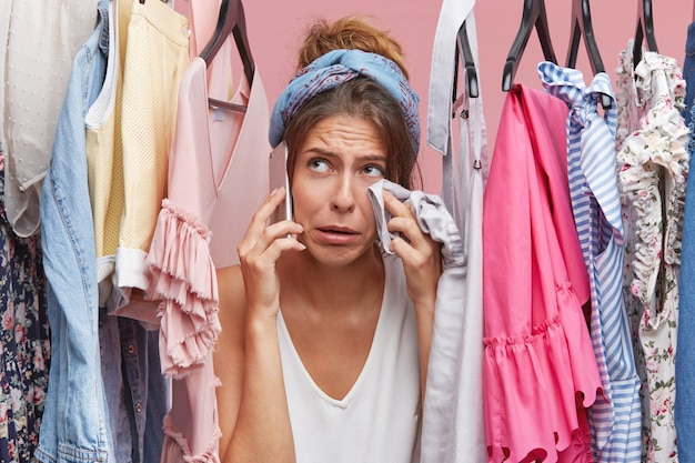 Huilende vrouw die haar gezicht met kleren afveegt terwijl ze in de buurt van haar garderobe staat, haar vriendin belt en klaagt dat ze niets te dragen en geen geld heeft om een nieuwe outfit te kopen. mensen, problemen, mode Gratis Foto