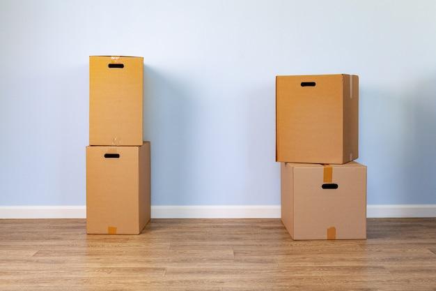 Huis bewegend concept met gestapelde kartondozen in een ruimte Premium Foto