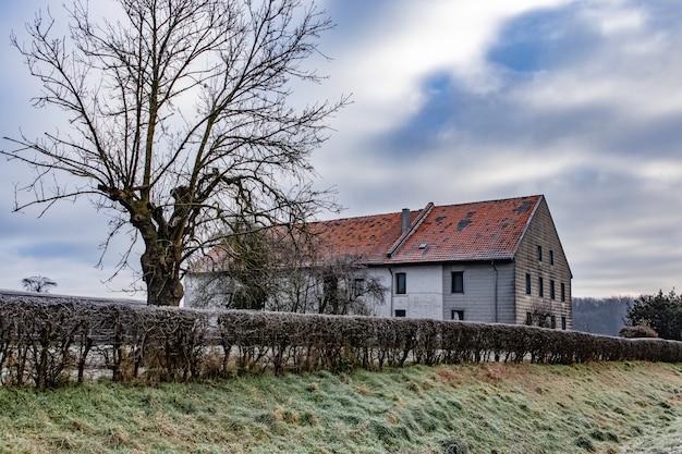 Huis omgeven door groen met heuvels onder een bewolkte hemel op de achtergrond Gratis Foto