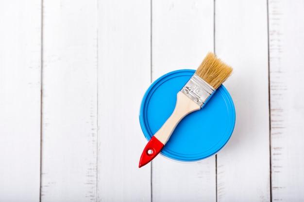 Huis renovatie concept. borstel en een verfemmer op witte sjofele houten planken. Premium Foto