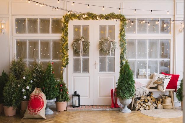 Huis versierd met kleine kerstbomen en lantaarns Premium Foto