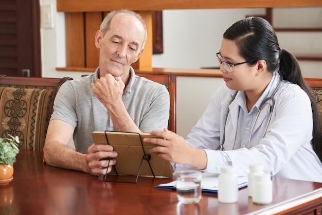 Huisarts die testresultaten toont aan oudere patiënt op tablet-pc Gratis Foto